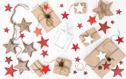 Christmas flat lay Wrapped gifts red stars decoration. Christmas flat lay. Wrapped gifts with red stars decoration on bright wooden background stock images