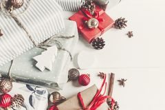 Christmas flat lay. wrapped presents with ornaments  and pine co. Nes anise and lights on rustic white wooden background top view. stylish gifts. seasonal Royalty Free Stock Image