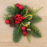 Christmas Floral Decoration. With red baubles, holly, ivy mistletoe and pine cones over oak wood background Royalty Free Stock Photography