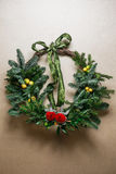 Christmas floral wreath decoration with baubles, red bow, holly and winter greenery over kraft background. Royalty Free Stock Photo