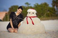 Christmas in Florida. Girl and sandman on the beach Stock Photos