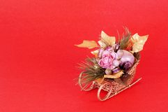 Christmas Flower Arrangement. Artificial flowers in a sleigh on red background with space for copy Royalty Free Stock Image