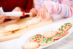Christmas: Focus On Decorated Christmas Cookies On Plate. Mother and child in various Christmas themed activities in the home Royalty Free Stock Images