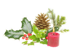 Christmas foliage with burning candle Stock Images