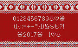 Christmas font. Knitted latin alphabet on seamless knitted pattern with snowflakes and fir. Nordic fair isle knitting, winter holi Royalty Free Stock Image