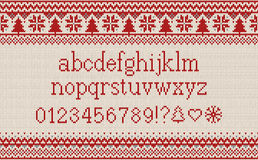 Christmas font. Knitted latin alphabet on seamless knitted pattern with snowflakes and fir. Nordic fair isle knitting, winter holi Stock Photography