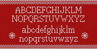 Christmas font. Knitted latin alphabet on seamless knitted pattern with snowflakes and fir. Nordic fair isle knitting. Winter holiday sweater design. Vector Stock Photo