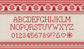 Christmas font. Knitted latin alphabet on seamless knitted pattern with snowflakes and fir. Nordic fair isle knitting. Winter holiday sweater design. Vector Stock Image