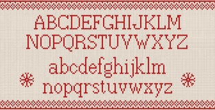 Christmas font. Knitted latin alphabet on seamless knitted pattern with snowflakes and fir. Nordic fair isle knitting, winter holiday sweater design. Vector Royalty Free Stock Images