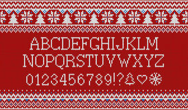 Christmas font. Knitted latin alphabet on seamless knitted pattern with snowflakes and fir. Nordic fair isle knitting Stock Photo