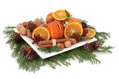 Christmas Food. Arrangement with dried orange fruit, nuts, spice and winter greenery over white background stock photo