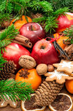 Christmas food background. Apples, cookies and spices. Christmas food background. Apples, mandarin fruits, walnuts, cookies and spices with green tree branches Royalty Free Stock Image