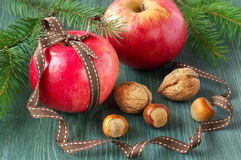 Christmas food background. Apples with nuts on wooden table. Stock Photo