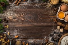 Christmas food background. Baking Ingredients. Fluor, eggs, butter, nuts, sugar, dried fruits on wooden table. top view. Copy space royalty free stock image