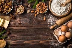 Christmas food background. Baking Ingredients. Fluor, eggs, butter, nuts, sugar, dried fruits on wooden table. top view. Copy space Stock Photos