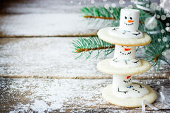 Christmas food background - cute melting snowmen cookies on snow. Y wooden background with Christmas tree branch blank space for text Royalty Free Stock Photography