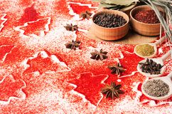 Christmas food background - different dry spices in wooden bowls on red christmas trees pattern, closeup, copy space. royalty free stock photos