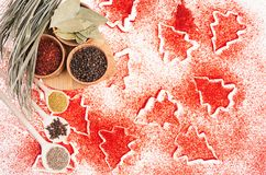 Christmas food background - different dry spices in wooden bowls on red christmas trees pattern, top view, copy space. royalty free stock images