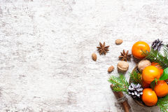 Christmas food background. tangerines. pine cones, nuts and spices. With fir branches on white wooden background with copy space. top view stock photo
