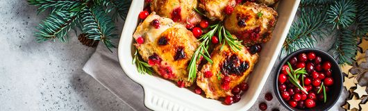 Christmas food. Baked Chicken meat with cranberries and rosemary in the oven dish, white background, banner