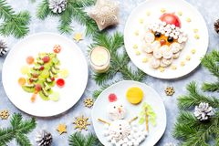 Christmas food for children - kiwi Christmas tree, marshmallow snowman, banana Santa Claus. Top view. Christmas food for children - kiwi Christmas tree royalty free stock image