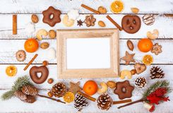 Christmas food flat lay with photo frame on white table. Christmas food flat lay on white board wood table with overload and chaotic arrangement, empty photo royalty free stock photo