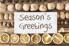 Christmas Food Flat Lay, Text Seasons Greetings. Sign With English Text Seasons Greetings. Christmas Food Flat Lay With Walnut, Hazelnut, Cinnamon Sticks And Stock Photos