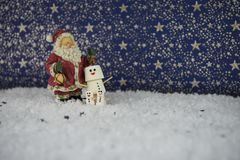 Christmas food photograph of marshmallows shaped as snowman in snow with stars pattern in background with Santa Claus decoration Royalty Free Stock Photo