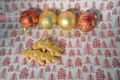 Christmas food photography gingerbread man men with red gold glitter tree decoration baubles on red festive wrapping paper. Studio food shot with gingerbread men Stock Images