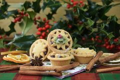 Christmas food photography image with mince pies cinnamon and oranges and cut holly leaves and berries on green red kitchen table Stock Photography