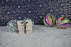 Christmas food photography of marshmallows shaped as a couple snowman standing in snow with colorful bauble decorations and stars stock photography