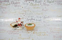 Christmas food photography mince pies and decoration jolly santa claus on xmas wrapping paper background Stock Photography