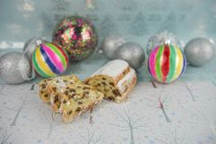 Christmas food photography picture with European stollen fruit bread cake and colorful bauble tree decorations in the background Stock Image