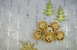 Christmas food photography picture with seasonal mince pies with glitter tree and star decorations on shiny silver background Royalty Free Stock Photos