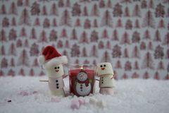 Christmas food photography using marshmallows shaped as snowman with iced on smile and red lit candle all standing in snow. Winter season Christmas photography Royalty Free Stock Images