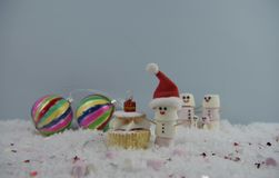 Christmas food photography using marshmallows shaped as snowman and standing in snow with cream sponge fairy cake and baubles Royalty Free Stock Photo