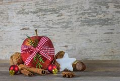 Christmas food, red apple, star cookie and aromatic spices. Christmas food gift, red apple, star cookie, nuts and aromatic spices on wooden table stock images
