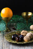 Christmas food still life: arabic dates, walnuts, persimmon Royalty Free Stock Photos