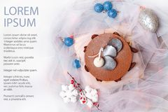 Christmas food still life with chocolate cake. Blue christmas balls and white snowflakes on white chiffon`s fabric background Stock Image
