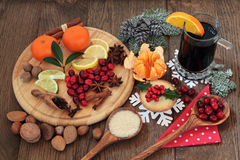 Christmas Food and Wine. Christmas food with mulled wine ingredients of citrus fruit and spices with nuts and mince pie over oak background Stock Photography