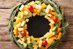 Christmas food: a wreath of pesto cheese, cheddar, mimolette wit. H tomatoes and rosemary close-up on the table. Horizontal top view from above stock photos