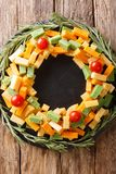Christmas food: a wreath of pesto cheese, cheddar, mimolette wit. H tomatoes and rosemary close-up on the table. Vertical top view from above stock photos