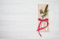 Christmas fork, knife and red ribbon on white wooden background Stock Photos
