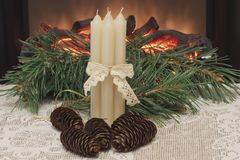 Christmas. Four white wax candles connected with an openwork ribbon, fir cones and pine branch on white openwork napkin against th royalty free stock photo