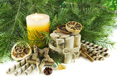 Christmas fragrances with conifer and candle. Christmas still life with burning candle, cinnamon sticks, dried oranges and natural conifer branches, isolated on Royalty Free Stock Photography
