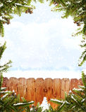 Christmas frame. Pine needles with cones and snow surround a fence with snowy background.  Small snowman sits at the bottom of the frame Royalty Free Stock Images