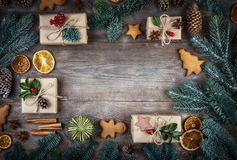 Christmas frame, background with decorations. Christmas gift, pine cones, fir branches, gingerbreads on wooden background. Retro royalty free stock photos