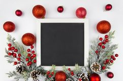 Christmas frame with christmas berry branches decorated with red balls. Flatly trandy mockup. Top view. Christmas frame with fir branches decorated with red and royalty free stock photography