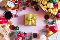 Christmas frame or border with a large assortment of christmas prop, decorations, balls, gifts and candles on a pink wooden stock photos