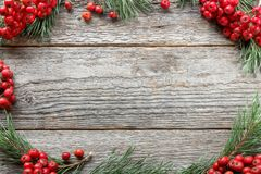 Christmas frame of the branches of the pine and red Rowan on wooden background. Copy space. Christmas frame of the branches of the pine and red Rowan on wooden Royalty Free Stock Photo